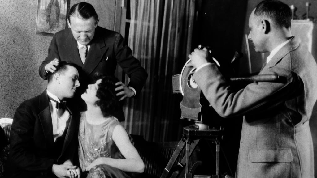"""Edmund Goulding """"ayudando"""" en la posición del beso de dos actores (1927)"""